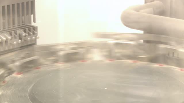 closeup pan shot of a stamping machine. - läkemedelsfabrik bildbanksvideor och videomaterial från bakom kulisserna