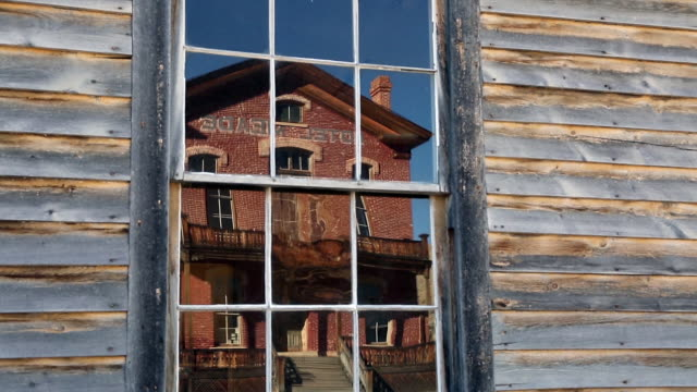 Closeup pan shot of reflection of old abandoned brick hotel in ghost town of Bannack, MT in window of faded paint wall.