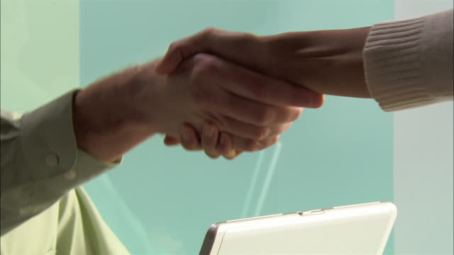 Close-up pan Young businessman and businesswoman shaking hands