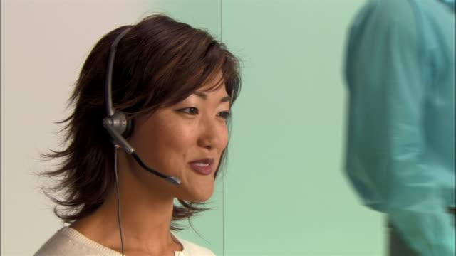 vídeos y material grabado en eventos de stock de close-up pan young businesswoman talking on headset and using desktop computer while businessman walks behind her in modern office - técnico telefónico