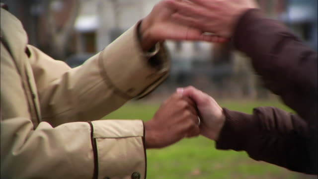 close-up pan young women giving each other street handshakes in park / williamsburg, brooklyn, new york, usa - スウィッシュパン点の映像素材/bロール