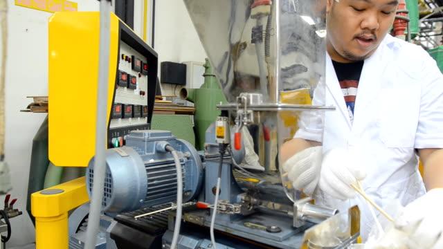 närbild panorering: en stor ung ingenjör Häll plastpärlor