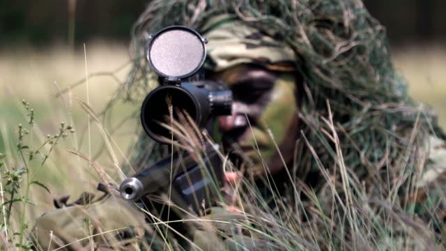 vídeos de stock e filmes b-roll de close-up panning :fully equipped and face and cloth-camouflaged sniper - camuflagem padrão