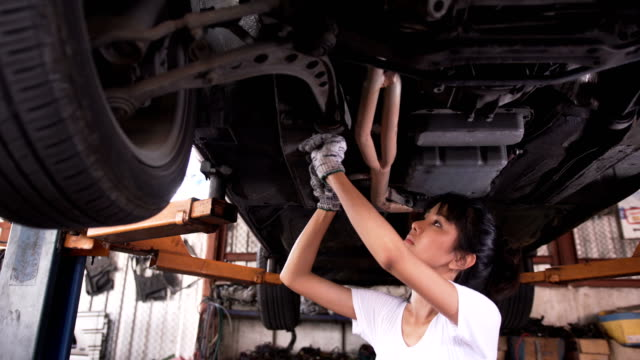 close-up panning low angle view: Young woman mechanic fixing by using wrench under car