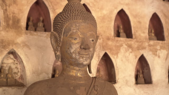 close-up panning of weathered buddha statue against wall at famous buddhist temple museum - vientiane, laos - weathered stock videos & royalty-free footage