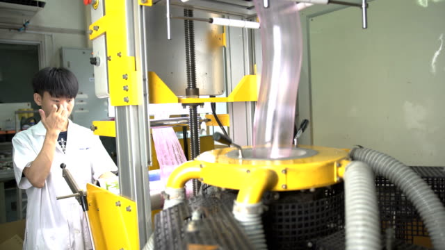 close-up panning: one young scientist control to collect film from blown film extruder