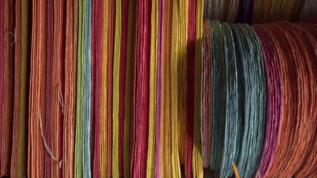 close-up panning shot of colorful threads arranged in store for sale - luang phabang, laos - off the beaten path stock videos & royalty-free footage