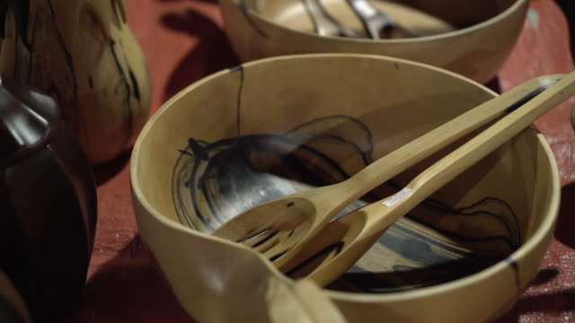 vidéos et rushes de close-up panning shot of wooden spoons in bowl at table for sale in store - luang phabang, laos - bol vide
