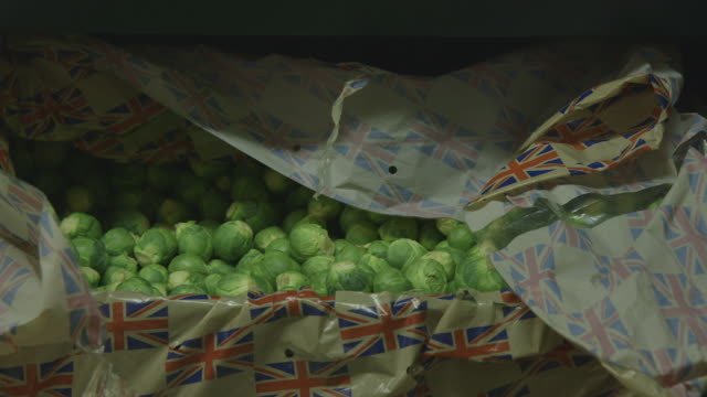 close-up panning shot onto a crate full of brussels sprouts in packaging emblazoned with the union jack. - brussels sprout stock videos & royalty-free footage