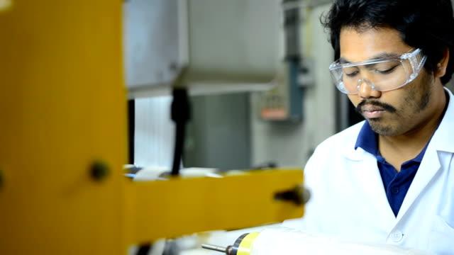 närbild panorering: ung ingenjör koncentrat att göra plastpåse fiilm