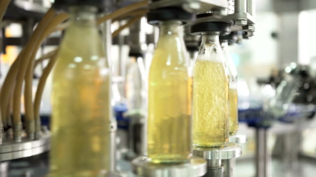close-up: part of automatic machine working all time for filling the herb beverage into glass transparent bottle - bottling plant stock videos & royalty-free footage