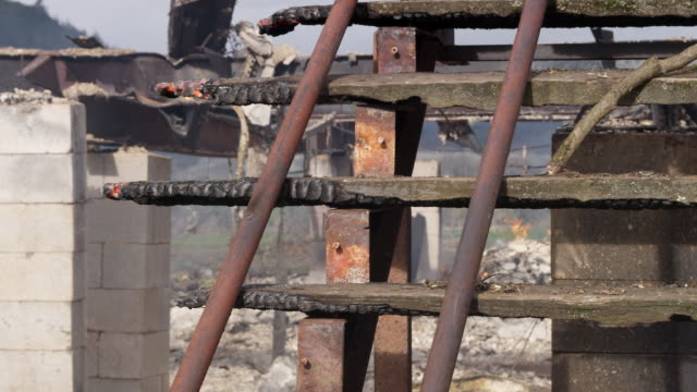 vidéos et rushes de close-up partially burned stairs and smoldering rubble in the aftermath of a house fire - parpaing
