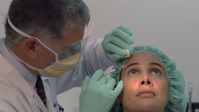 vídeos de stock e filmes b-roll de close-up plastic surgeon injecting botox into woman's forehead/ panama city, panama  - tratamento a laser