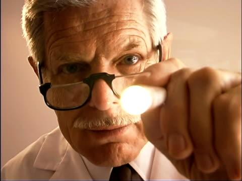 vídeos de stock, filmes e b-roll de close-up point of view of doctor holding light to look into mouth during medical exam. - menos de 10 segundos