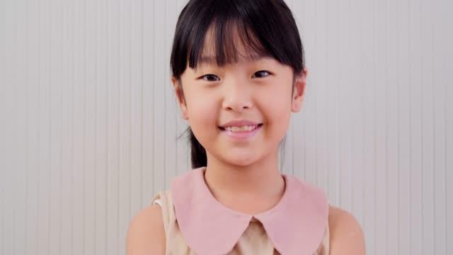 nahauf-porträt schöne kleine mädchen mit blick auf die kamera und lächelt freundlich - childhood stock-videos und b-roll-filmmaterial