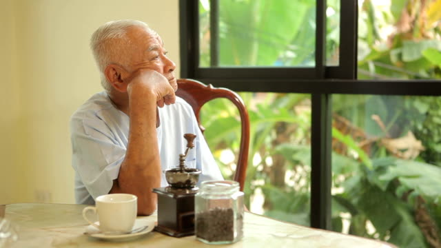 close-up portrait of a asian senior man thinking at home - sad old asian man stock videos & royalty-free footage