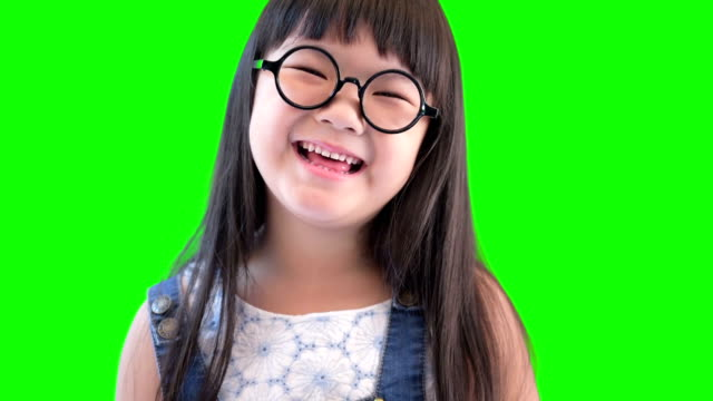 Close-up portrait of a happy little girl bursting in laugh on green screen