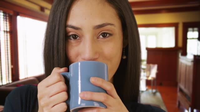 a close-up portrait of a hispanic woman drinking coffee - カフェイン分子点の映像素材/bロール