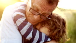 Closeup portrait of a mature man hugging his late son. Happy fatherhood. Curly child, a man wearing optical glasses. Colorful sunset