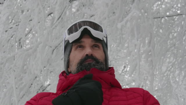 close-up portrait of a mature man putting his ski googles on in the snow at a ski resort. enjoying the winter mountain. preparing for skiing in the snow white mountains. downhill skiing. - ski goggles stock videos & royalty-free footage