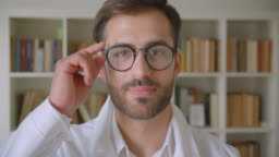 Closeup portrait of adult handsome caucasian businessman in glasses looking at camera in the library with bookshelves on the background indoors