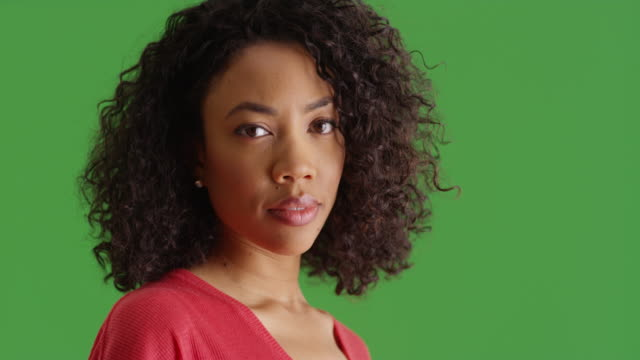 vidéos et rushes de close-up portrait of african american woman in red shirt on greenscreen - bouche humaine