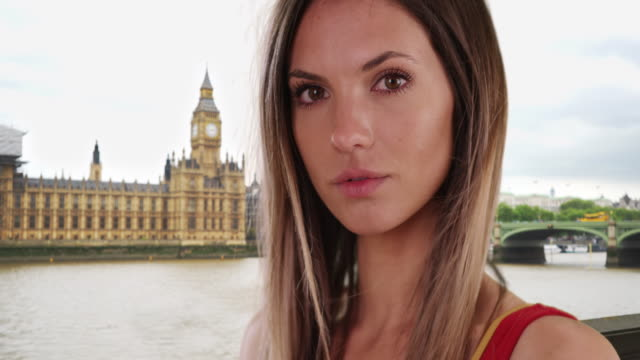 close-up portrait of brunette with wind blowing hair by big ben in london - big hair stock videos & royalty-free footage