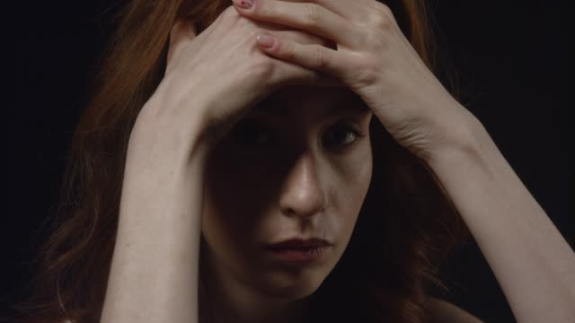 closeup portrait of depressed young caucasian female looking at camera and on the sides being close to start crying - redhead stock videos & royalty-free footage
