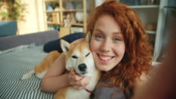 Close-up portrait of girl and dog lying on couch kissing looking at camera
