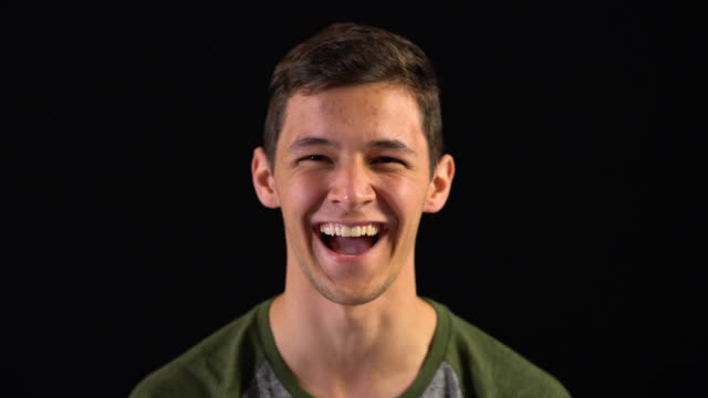 close-up portrait of happy young man - studio shot stock videos & royalty-free footage
