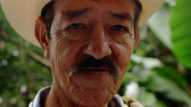 close-up portrait of mexican farmer with jungle backdrop - produttore video stock e b–roll