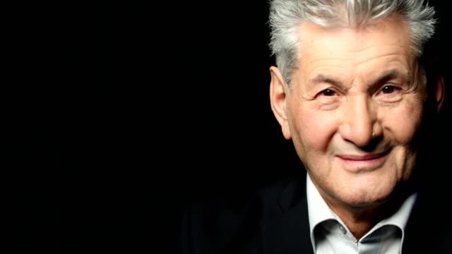stockvideo's en b-roll-footage met close-up portret van senior zakenman glimlachen - formeel portret