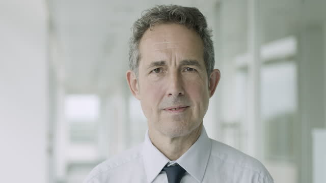 close-up portrait of senior male doctor standing in hospital corridor looking at camera wearing shirt and tie - shirt and tie stock videos & royalty-free footage