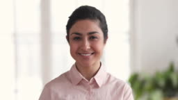 Closeup portrait of smiling millennial indian business woman in office