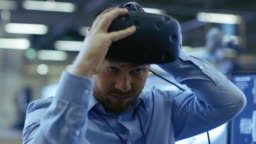 Close-up Portrait of the Industrial Engineer Putting on Virtual Reality Headset, ready to Work. In the Background Manufacturing Plant and Monitors.