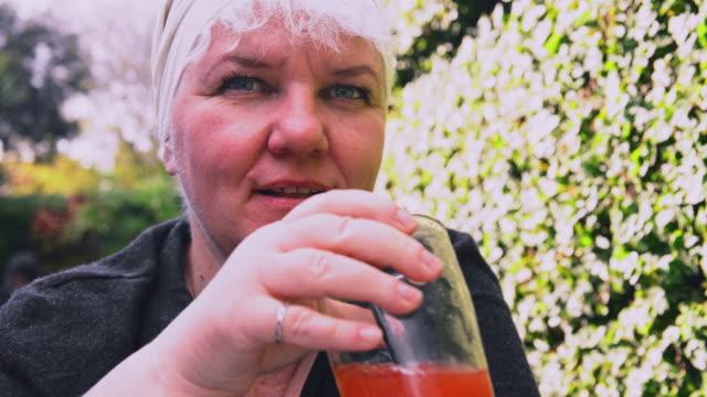 vídeos de stock, filmes e b-roll de retrato do close up do maduro, corpo alegre-positivo mulher caucasiano que bebe suco sangrento de mary em um café ao ar livre. - body positive