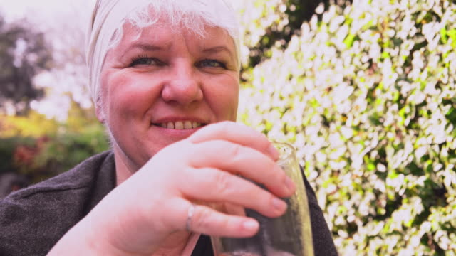 closeup portrait of the mature, cheerful body-positive caucasian woman drinking tomato juice in an open-air cafe. - body positive stock videos and b-roll footage