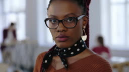Close-up portrait of young beautiful serious black business woman in eyeglasses looking at camera at office workplace.