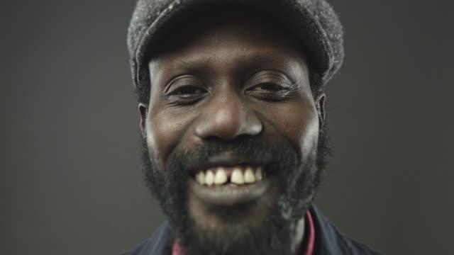Vidéo Close-up portrait d'homme africain regardant sourire caméra