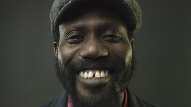 Close-up portrait video of african man looking at camera smiling
