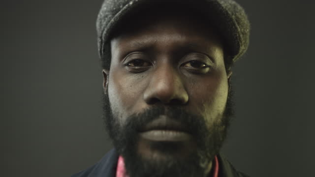 Close-up portrait video of african man looking at camera