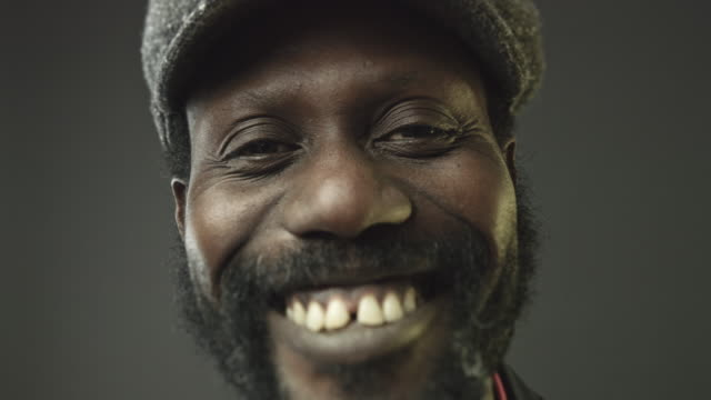 Close-up portrait video of smiling well dressed african man looking at camera