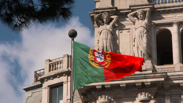 close-up: portuguese flag and two statues on a building - portugal stock-videos und b-roll-filmmaterial