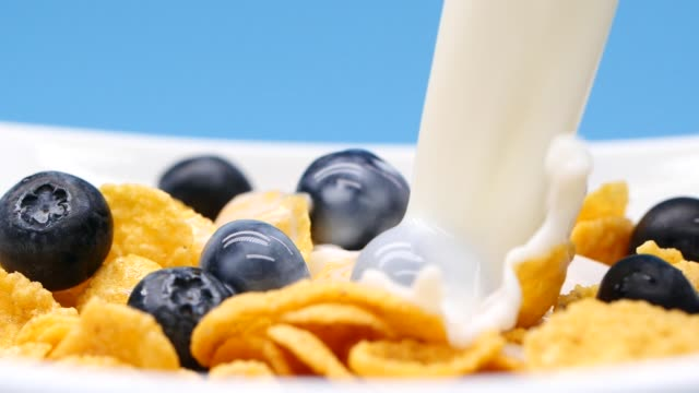 close-up pouring milk into a bowl with cereals and blue berries, slow motion - oatmeal stock videos & royalty-free footage