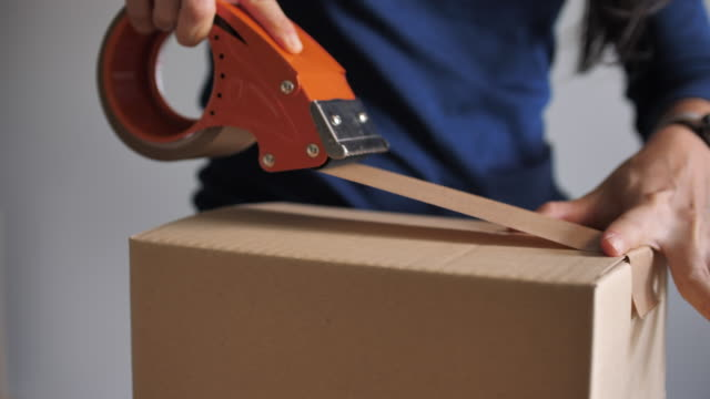 close-up professional warehouse worker finishes order, sealing cardboard boxes ready for shipment - e commerce stock videos & royalty-free footage