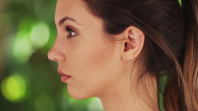 close-up profile of beautiful model posing on green and white background - profil redigerat segment bildbanksvideor och videomaterial från bakom kulisserna