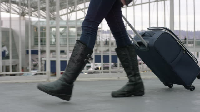 Close-Up Profile Shot of a Professionally Dress Woman Pulling a Suitcase on a Sky Bridge