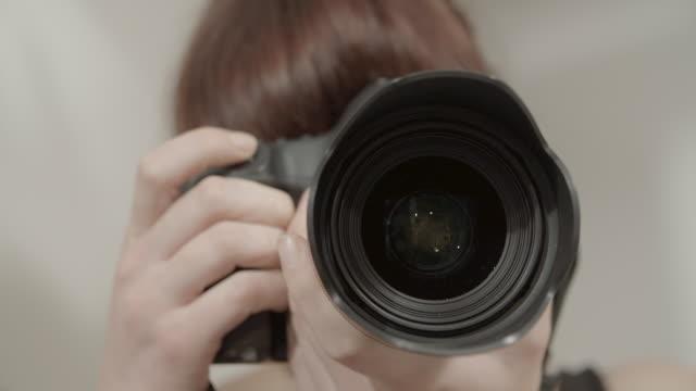 close-up rack focus shot of woman photographing with dslr camera - paris, france - デジタル一眼レフカメラ点の映像素材/bロール