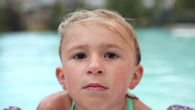 closeup rack-focus of a little girl in a pool. - schwimmflügel stock-videos und b-roll-filmmaterial