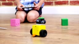 close-up, radio-controlled robot moves on floor, little geniuses, children play electronic robots, cars, modern toys on radio control. new technologies in gaming industry